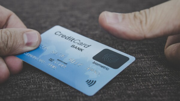 Close up of male hands holding credit card with fingerprint scanner and embedding the thumb to pay online. Concept of using biometric technology in banking.