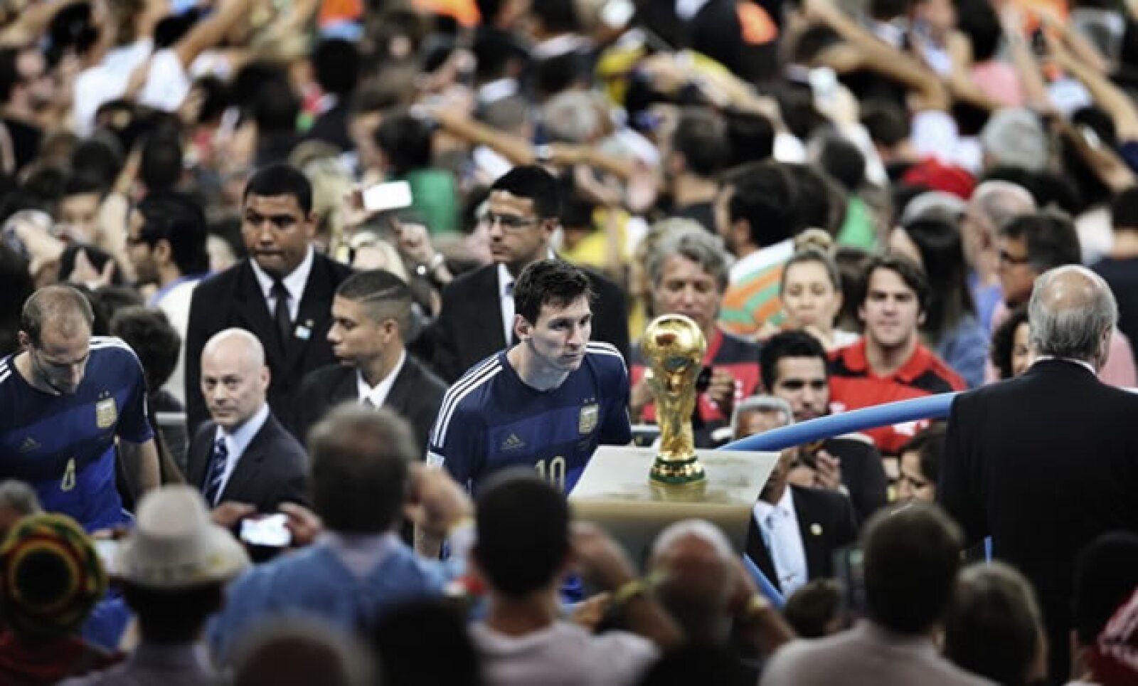Lionel Messi pasa junto al trofeo de la Copa del Mundo en el estadio Maracana durante el Mundial de Brasil. Autor: Bao Tailiang. Categoría: Deportes.