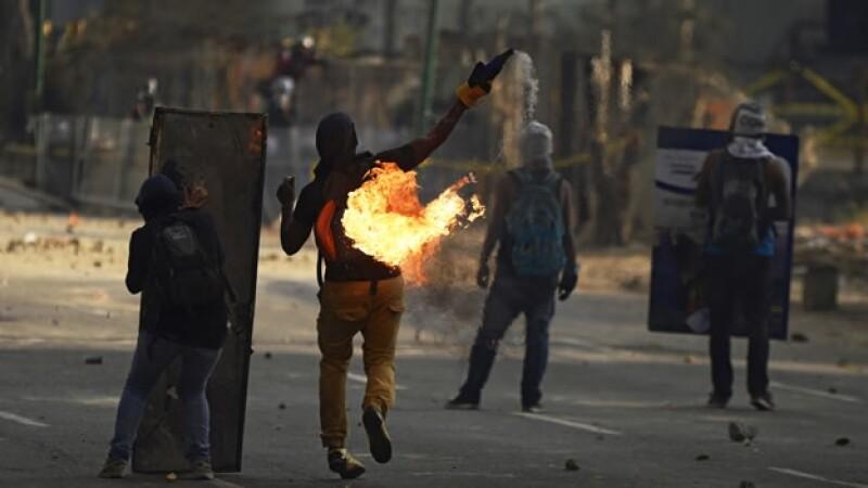Manifestantes en Caracas, Venezuela, lanzan un artefacto explosivo durante