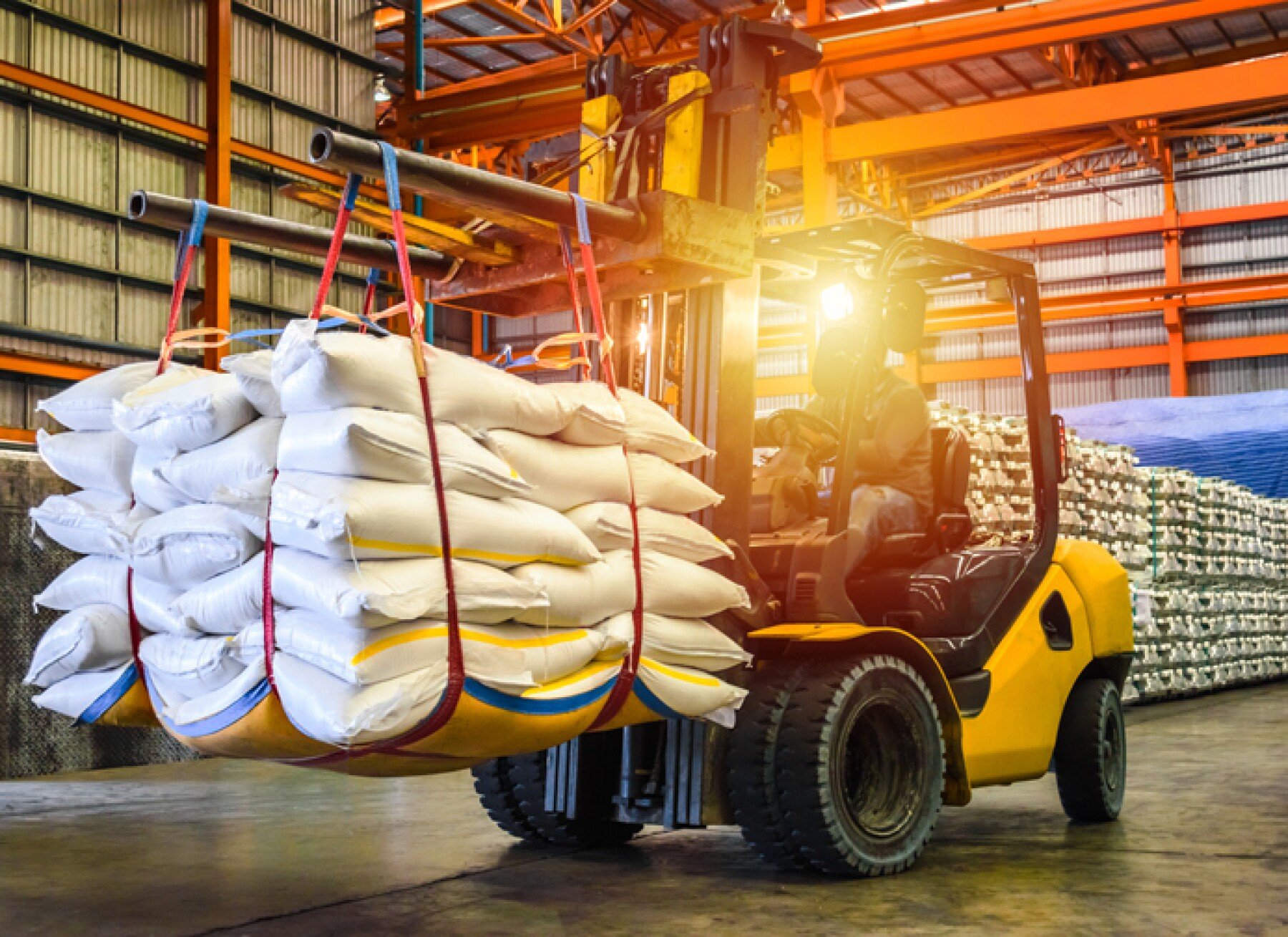 Forklift handling sugar bags for stuffing into container for export.