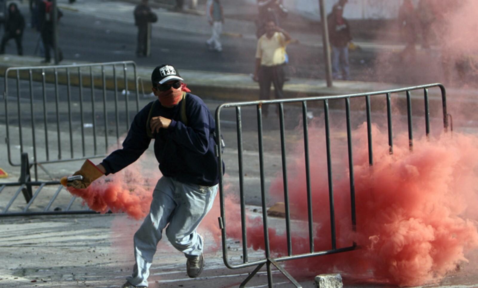 Los manifestantes lanzaron petardos e intentaron romper el cerco de las vallas metálicas colocado en la zona de San Lázaro para resguardar la Cámara de Diputados.