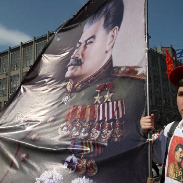 Seguidores del partido Comunista ruso portan banderas e imágenes del dictador soviético Josef Stalin durante una marcha en Moscú