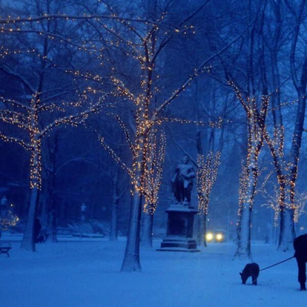 Una intensa tormenta de nieve azota el noreste de Estados Unidos. Una mujer juega con su perro en Boston, Massachusetts.