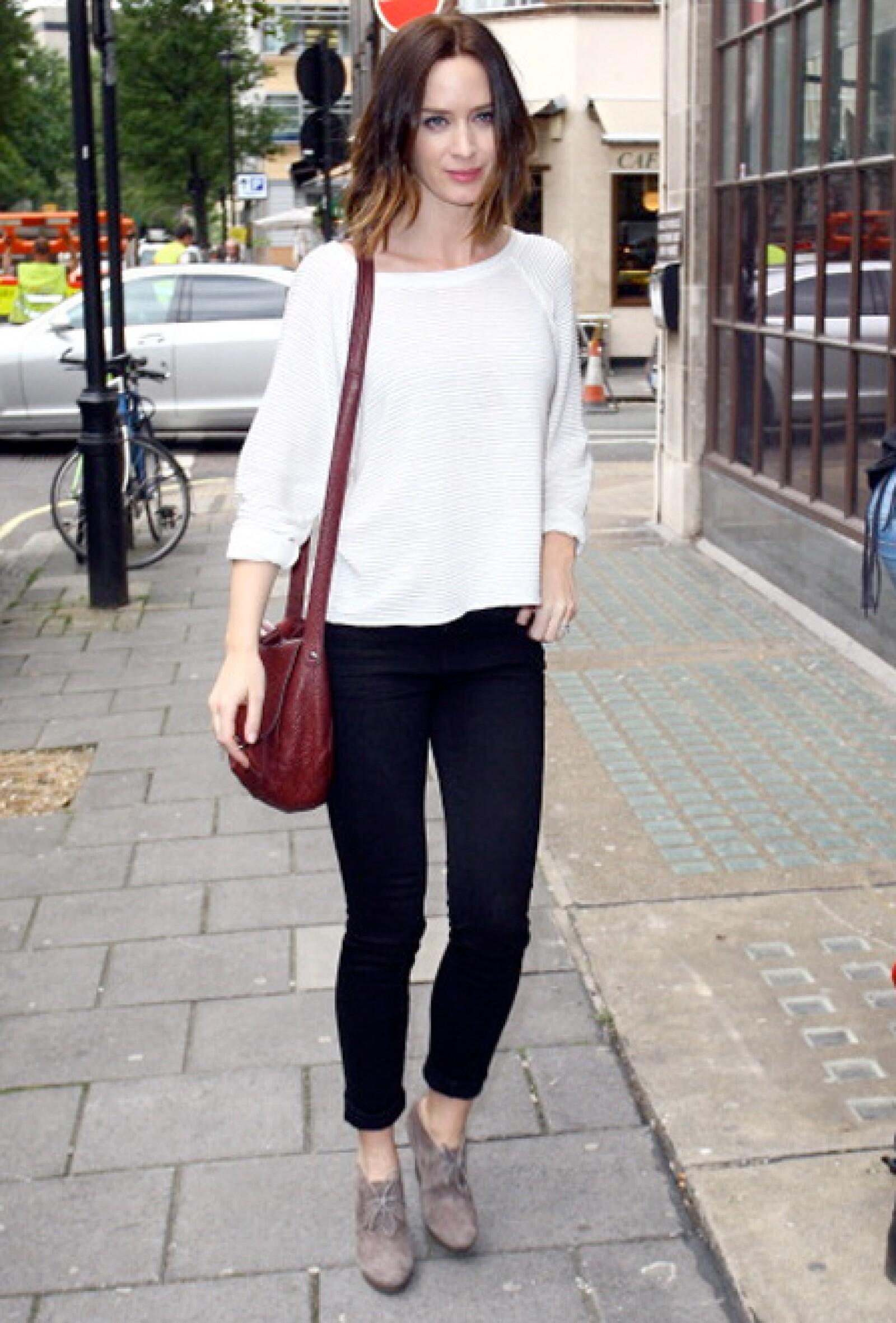 Emily Blunt combina un suéter blanco a la forma básica con unos pantalones negros.