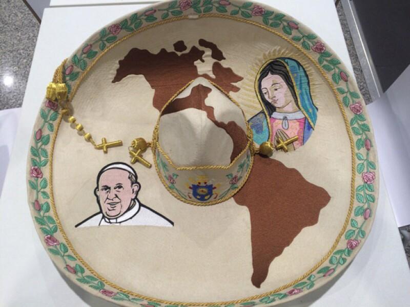 El sombrero tiene las imágenes de Juan Pablo II y la Virgen de Guadalupe.
