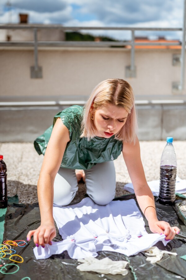 Young adult woman making tie dye clothes outdoors on the rooftop