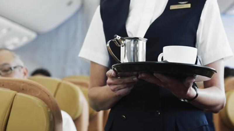 una azafata sirve el cafe en un avion