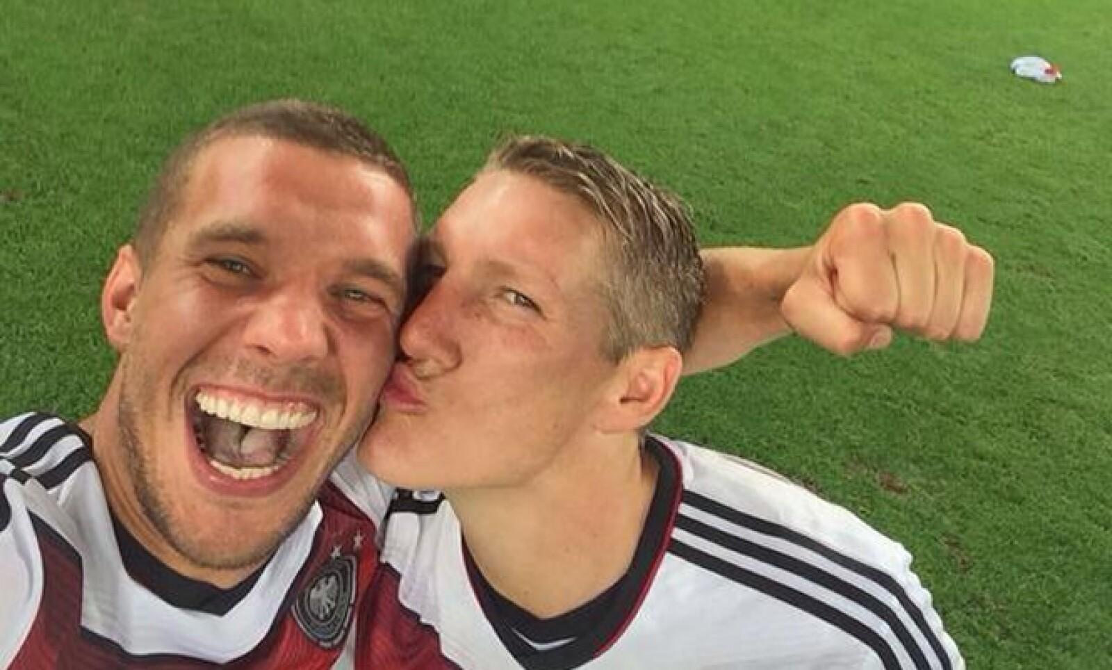 Podolski  recibe un beso de Bastian Schweinsteiger en la celebración de la Copa del Mundo.