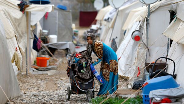 FILE PHOTO: A Syrian refugee mother puts her baby into a stroller in Nizip refugee camp