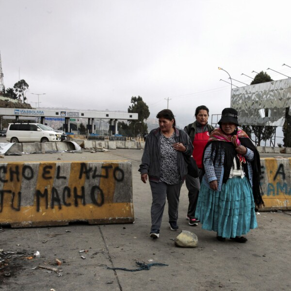 People walk past roadblocks after last night's protests, following Bolivia's former president Evo Morales' exit out of the country, in El Alto