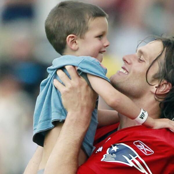 Tom Brady, mariscal de campo de los Patriotas de Nueva Inglaterra, carga a su hijo Jack luego de un entrenamiento con el equipo.