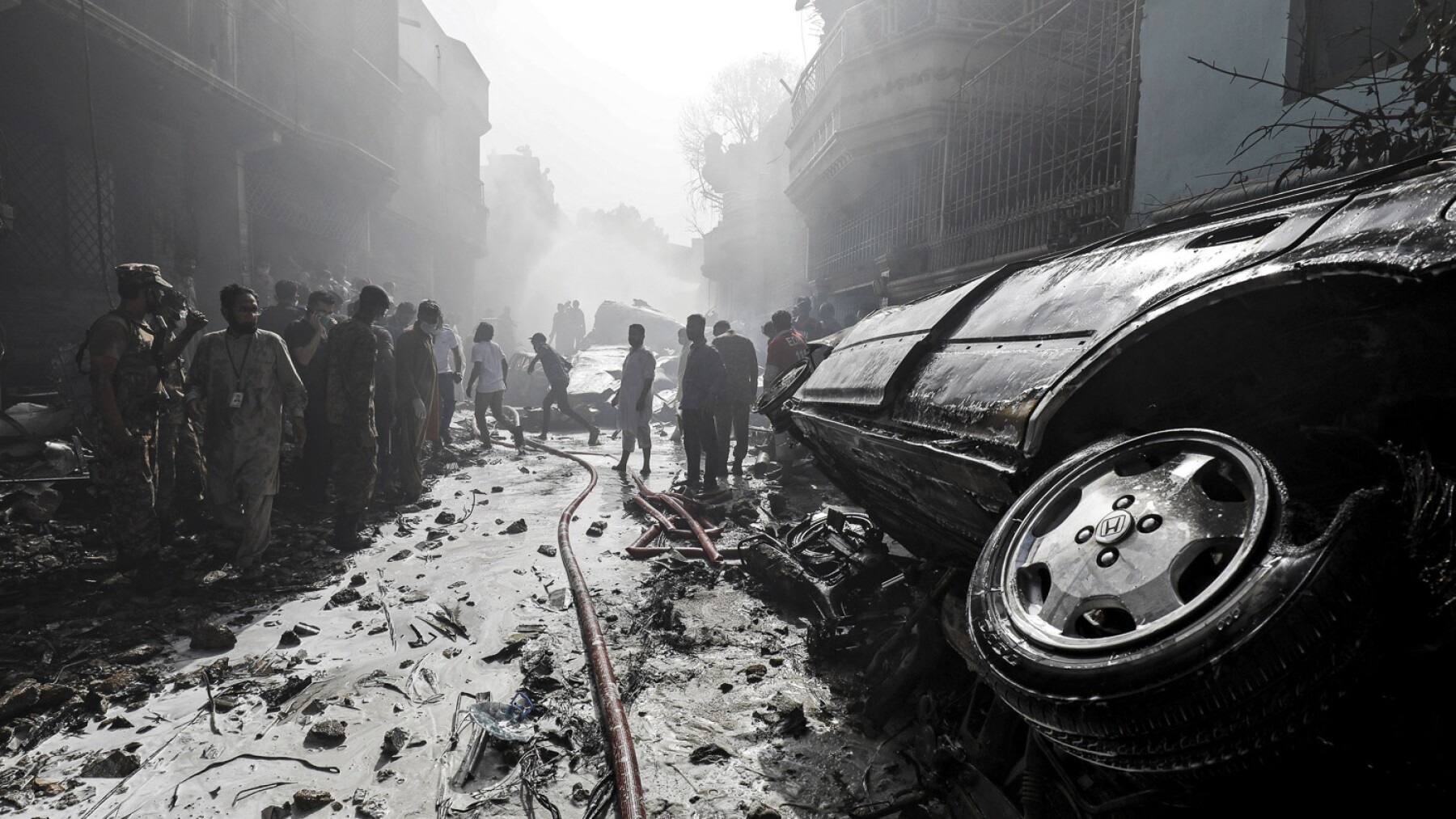 Rescue workers gather at the site of a passenger plane crash in a residential area near an airport in Karachi