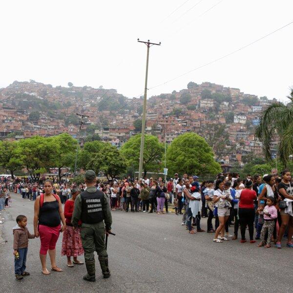 Soldados venezolanos montan guardia en una calle afuera de un supermercado mientras la gente hace cola para comprar algunos alimentos básicos.