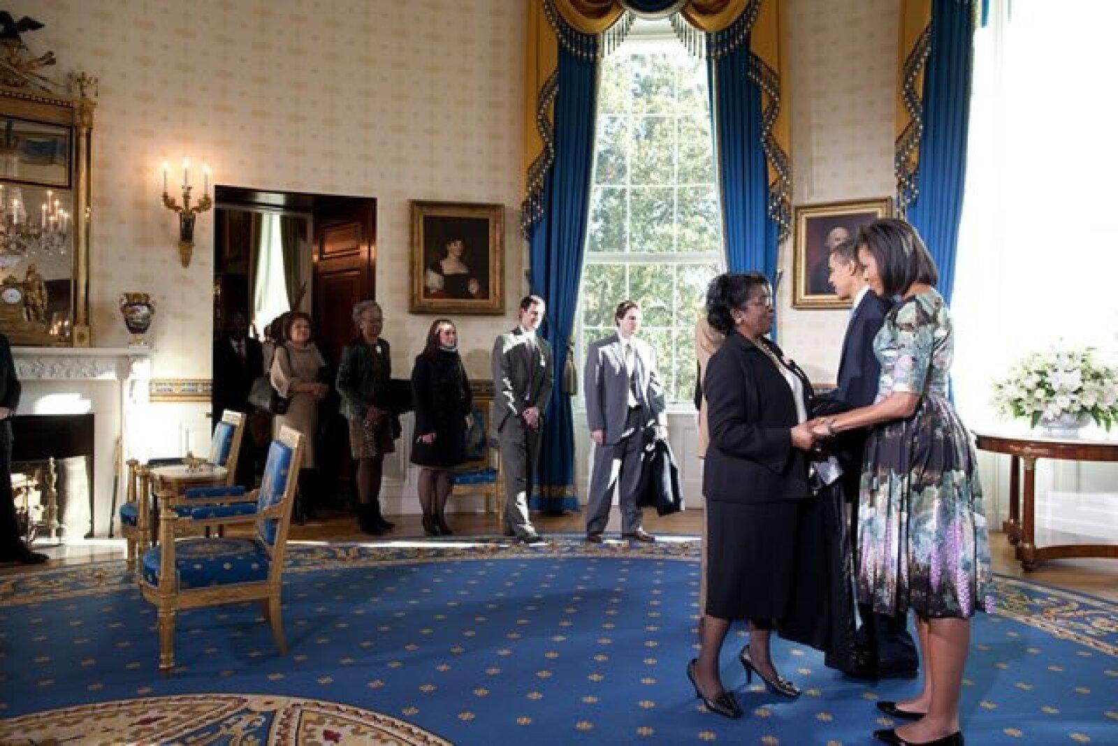El presidente y la primera dama, Michelle Obama, dan la bienvenida a algunos visitantes en la Sala Azul de la Casa Blanca.