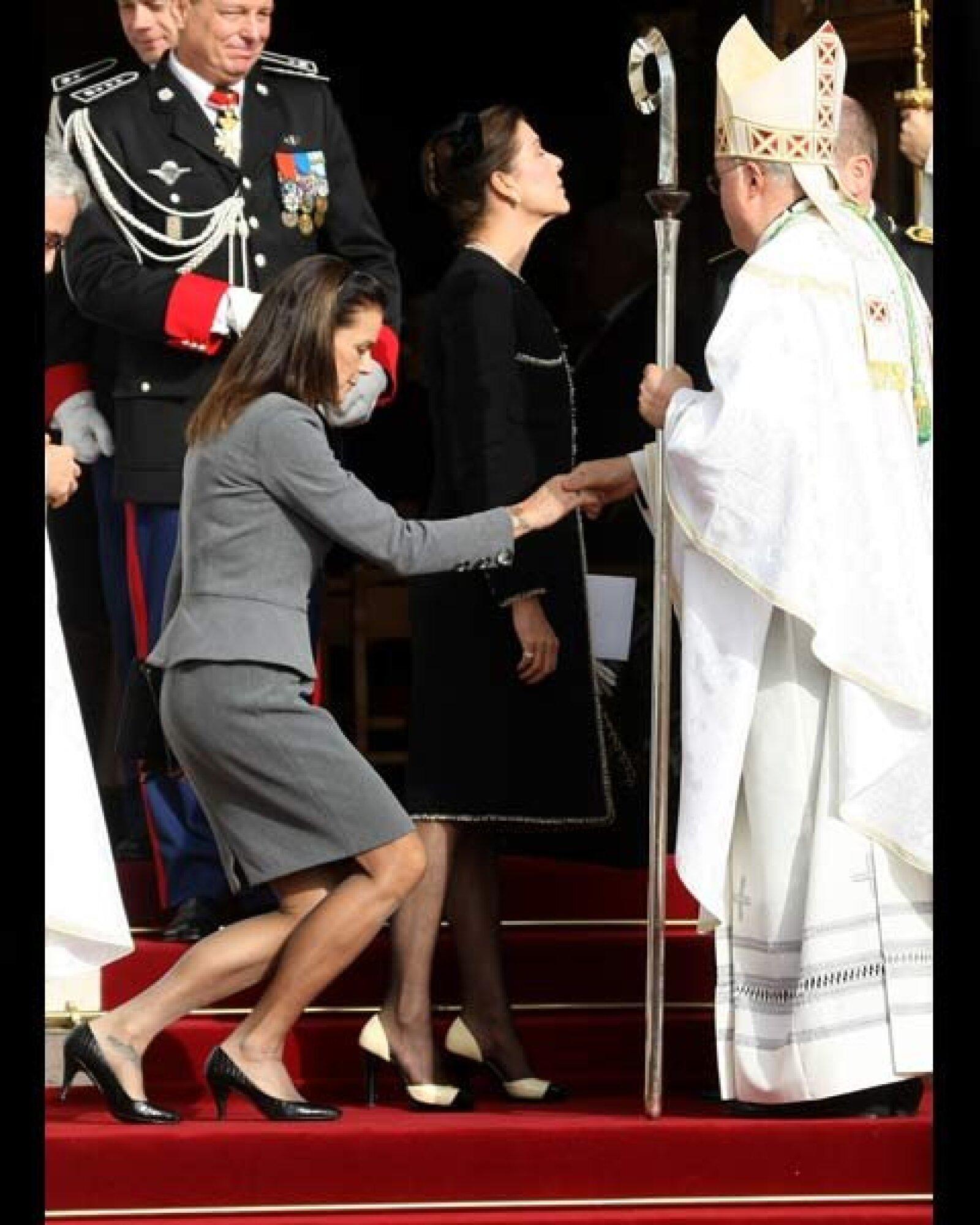 La Princesa Estefanía de Mónaco se prepara para besar la mano del arzobispo Bernard Barsi.
