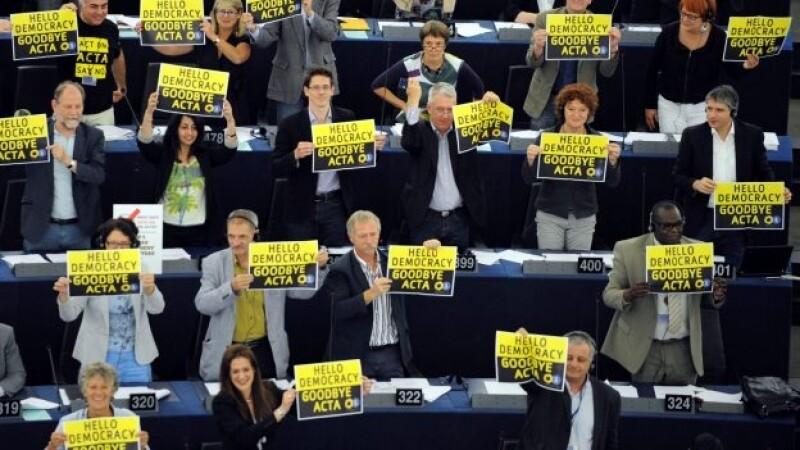 """Eurodiputados de Los Verdes muestran carteles con el mensaje """"Hola democracia. Adiós Acta"""" después de que el pleno del Parlamento Europeo rechazase el acuerdo"""