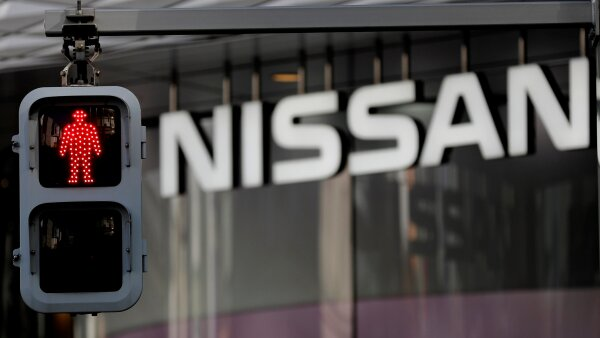 Nissan's signboard is seen behind a traffic sign at its showroom in Tokyo