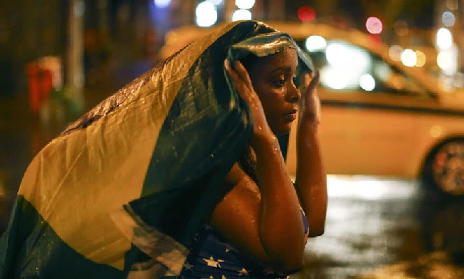 Una mujer mira al vacío en las calles de Rio al saber que su selección ha sido eliminada de la manera más contudente que pudo haber imaginado.