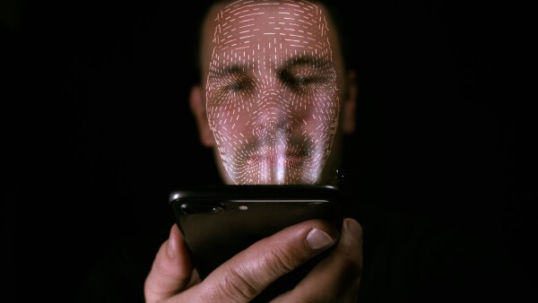 Male using his smart phone with facial recognition unlock. 3D mesh print is projected onto his face.
