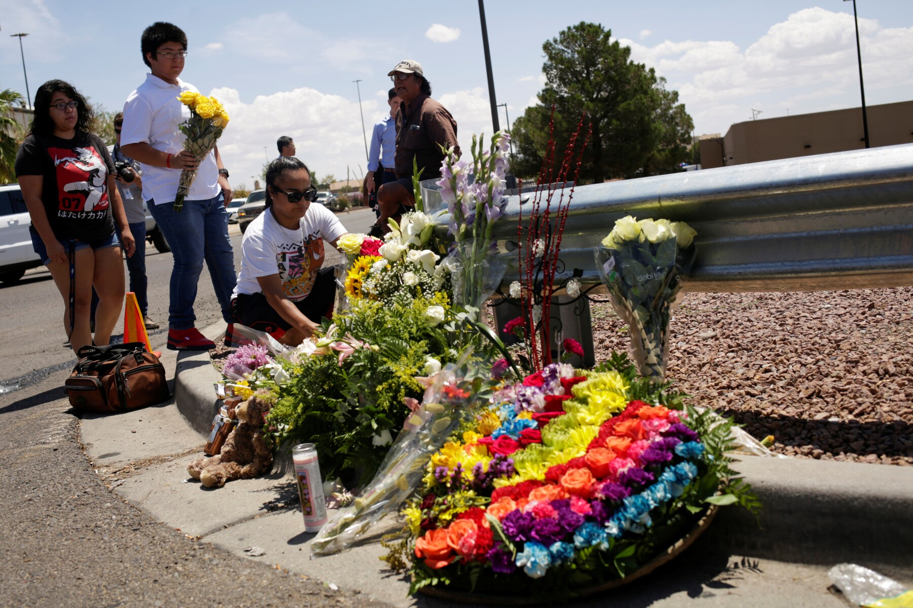 People place flowers at the site of a mass shooting where 20 people lost their lives at a Walmart in El Paso