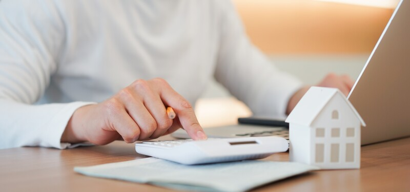 close up young man hand press on calculator to check and summary expense of home loan mortgage for refinance plan , people lifestyle concept
