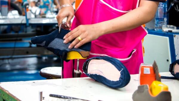 worker making shoe in footwear production line