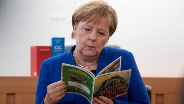 FILE PHOTO: German Chancellor Angela Merkel leafs through an instructional booklet about Germany's constitution being used in a school class for recently arrived migrants