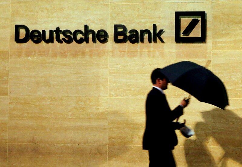 FILE PHOTO: A man walks past Deutsche Bank offices in London