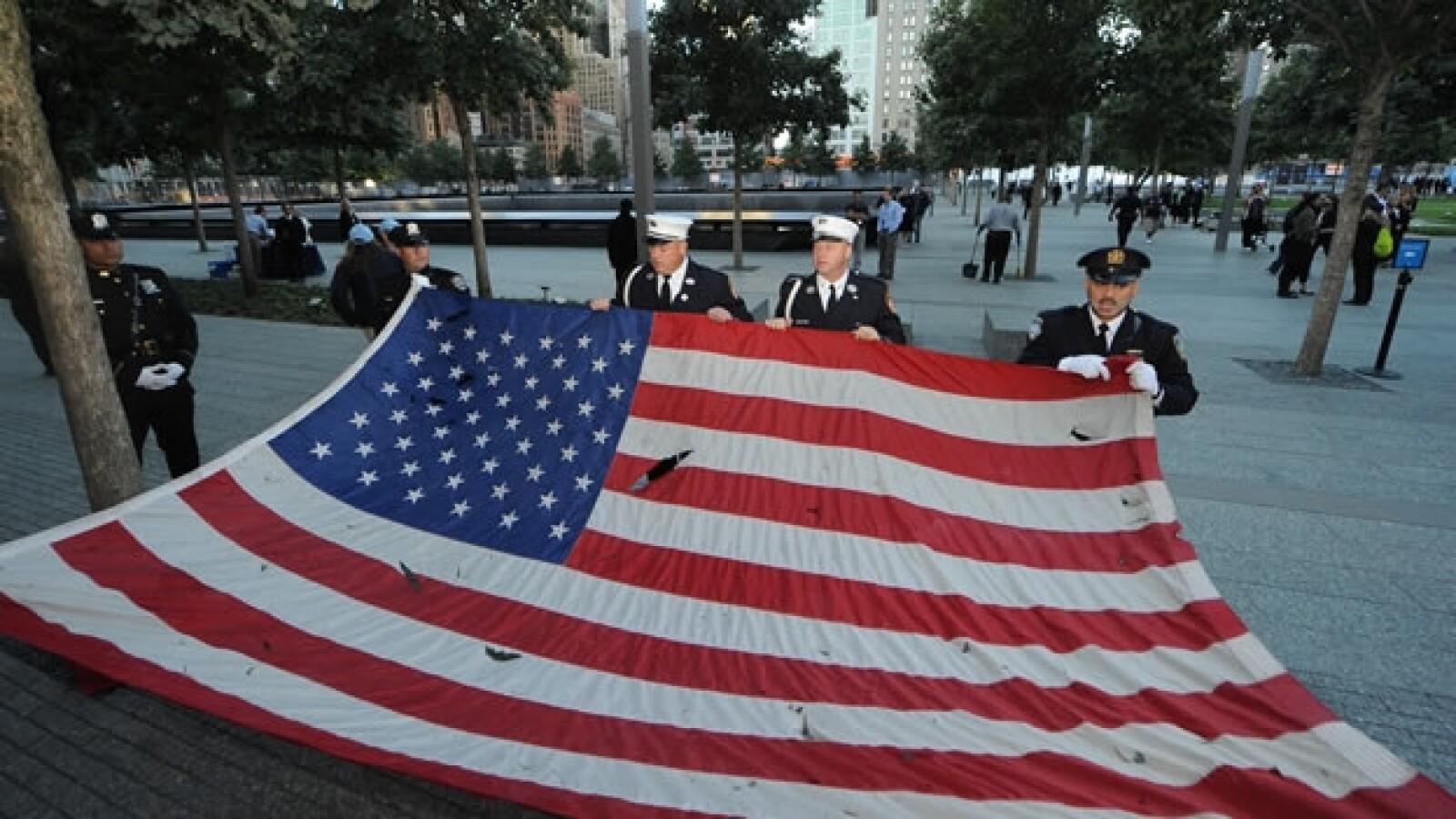 La policía de Nueva York pasea una bandera recogida de los ataques terroristas