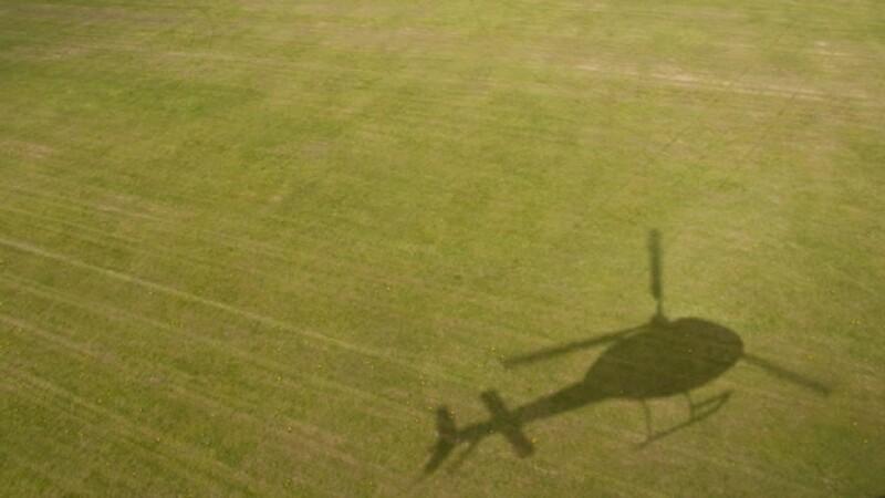 sombra de un helicoptero sobre un campo