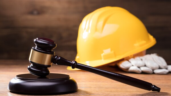 Gavel In Front Of Yellow Safety Helmet