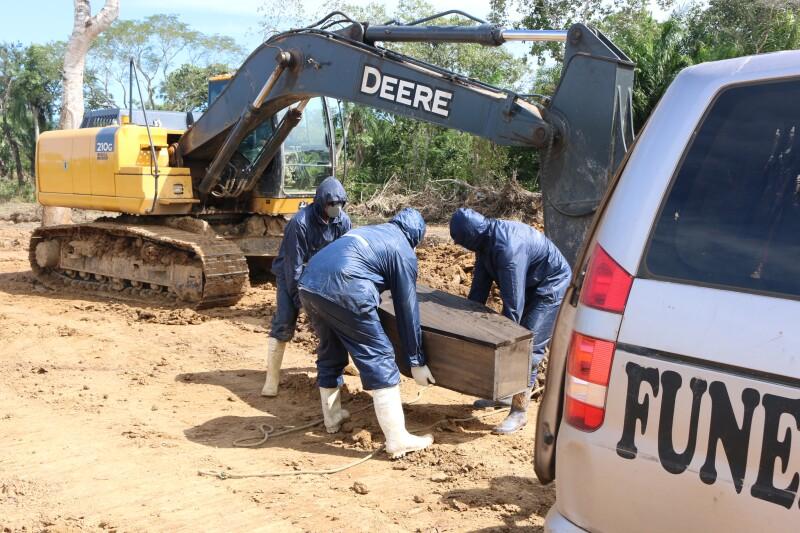 Trabajadores de una funeraria de Bolivia levantan un ataúd para llevarlo a una fosa recién cavada en Beni para víctimas de COVID-19. Crédito: Ricardo Gutiérrez