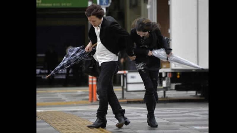una pareja joven intenta caminar en  medio del los fuertes vientos