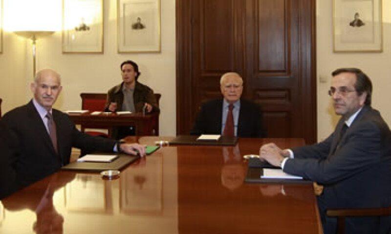 El primer ministro George Papandreou (i) y el líder Antonis Samaras (d) se reunieron con el presidente Karolos Papoulias (c) este domingo. (Foto: Reuters)