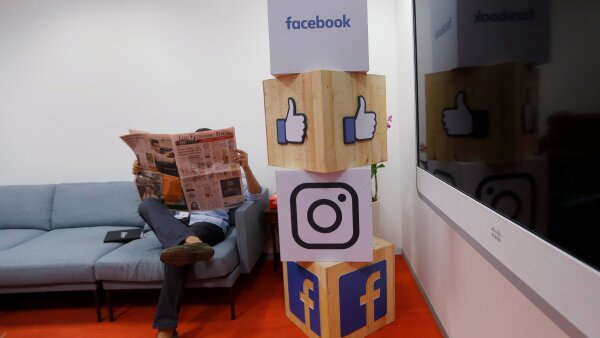 FILE PHOTO: A man reads a newspaper at the reception area of Facebook's new office in Mumbai