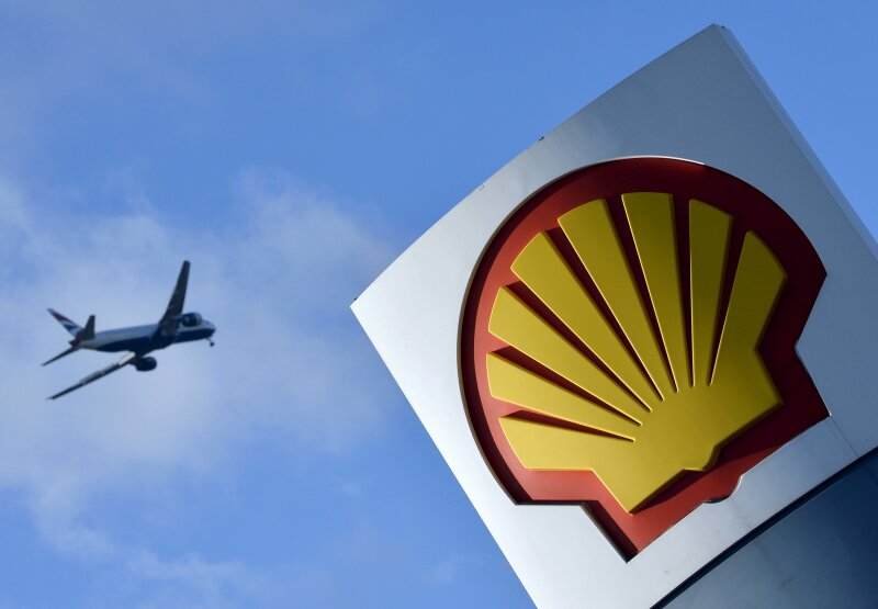 FILE PHOTO: A passenger plane flies over a Shell logo at a petrol station in west London, Britain