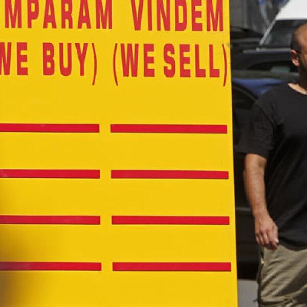 Un hombre pasa a un lado de un tablero con datos del cambio de divisas en Bucarest. Las acciones europeas pasaban a pérdida el lunes.