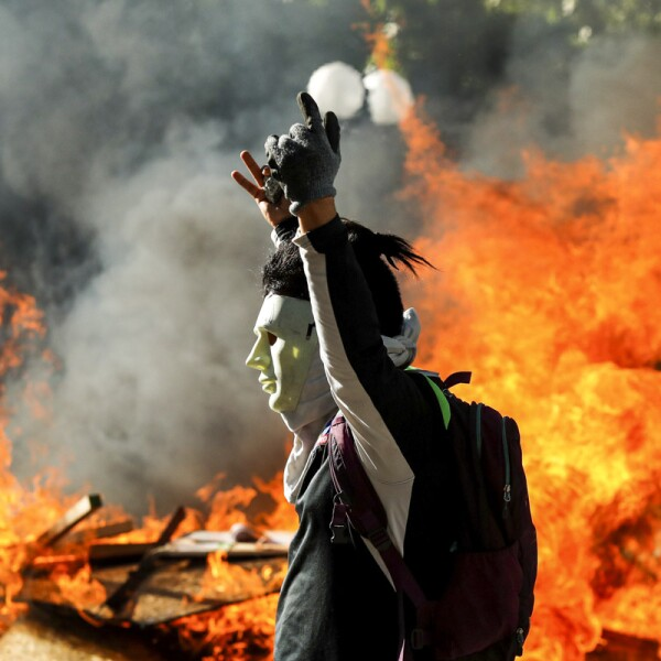 A masked demonstrator gestures in front of a burning barricade during a protest at Providencia, a wealthy neighborhood, in Santiago