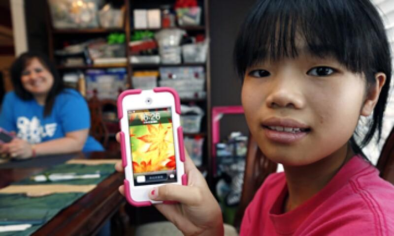 Guan Ya muestra el dispositivo que usa para traducir y comunicarse con su familia adoptiva. (Foto: AP)