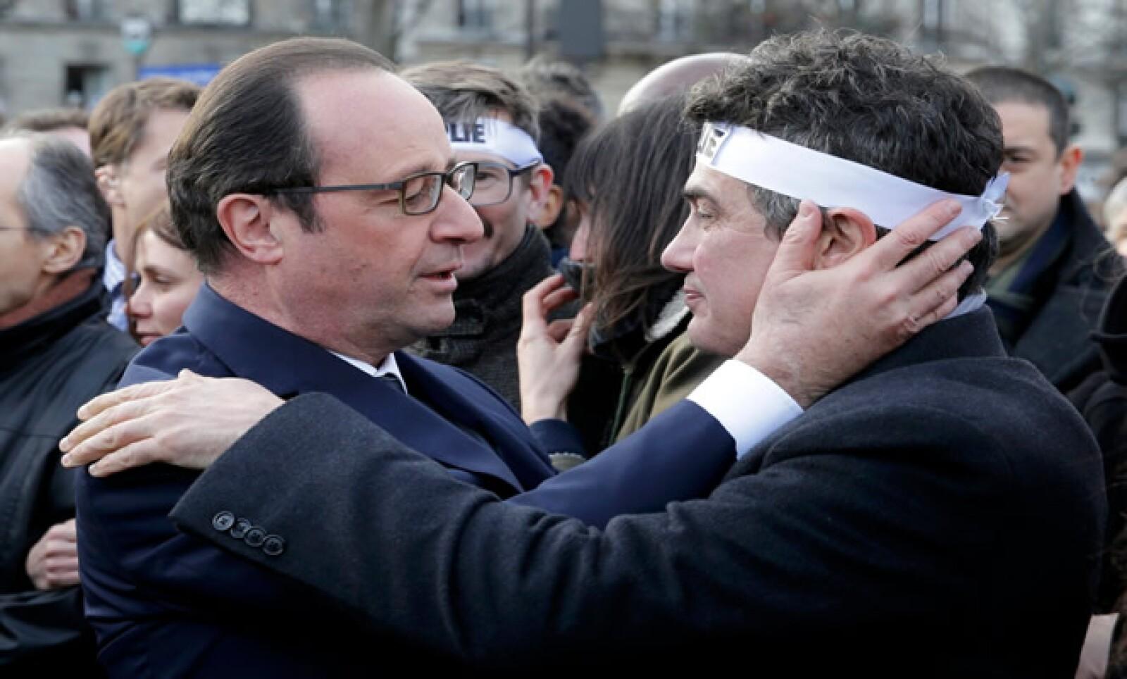 El mandatario consuela al columnista de Charlie Hebdo Patrick Pelloux durante la marcha en la que participaron familiares y parientes de las víctimas.