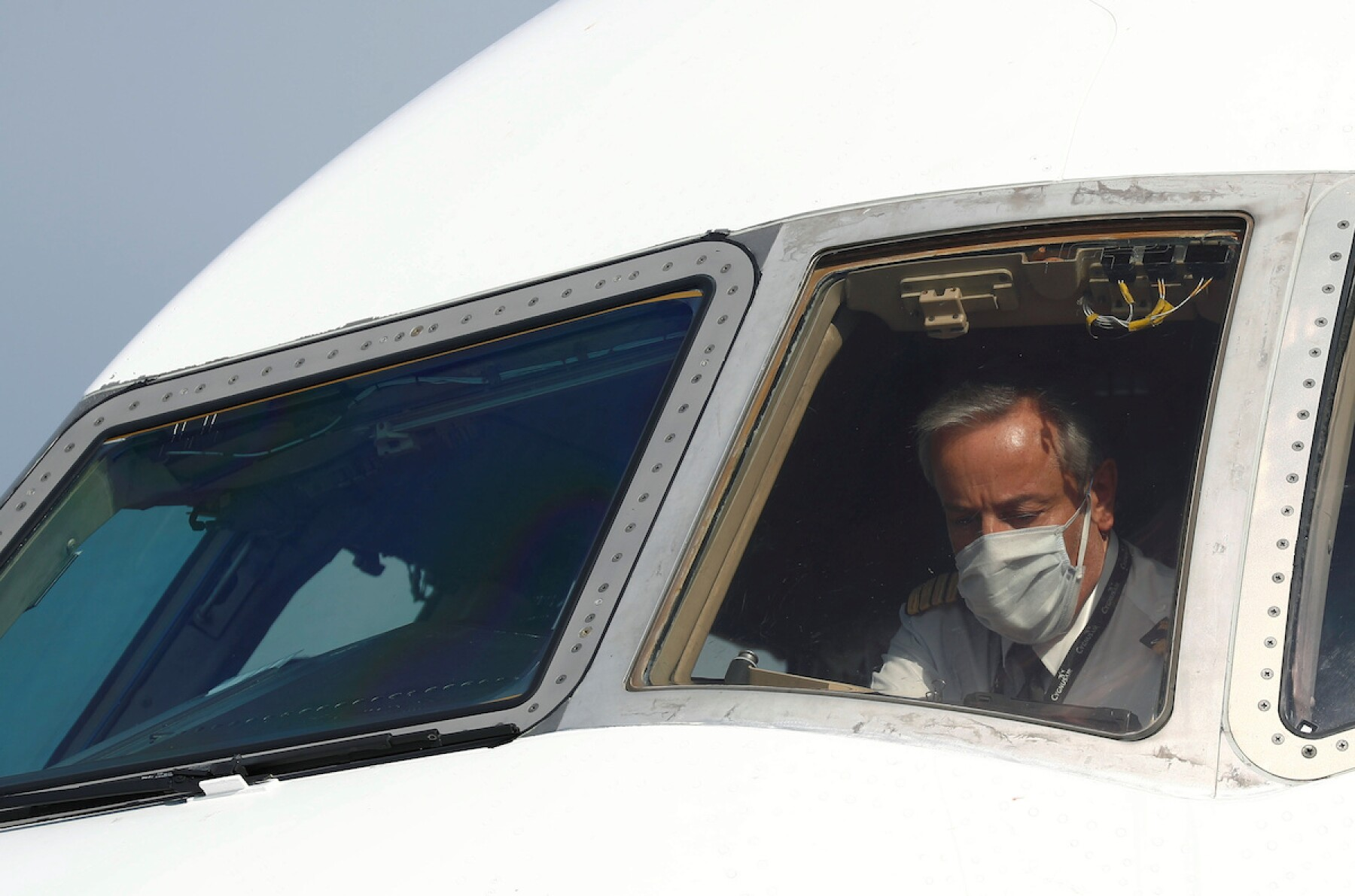 A pilot wearing a protective mask is seen in a cargo aircraft at Liege airport