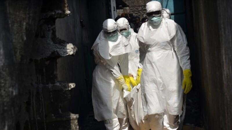 Trabajadores de la Cruz Roja cargan el cuerpo de una víctima del ébola en Monrovia, Liberia