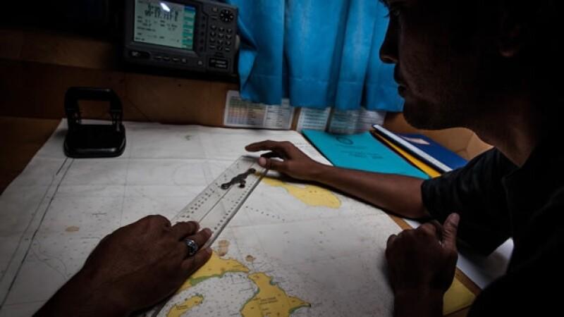 Trabajadores del Equipo Nacional de Búsqueda y Rescate de Indonesia observan un mapa durante una búsqueda del avión desaparecido