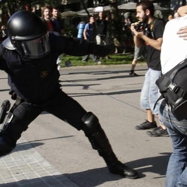 un policia se prepara para golpear a un manifestante