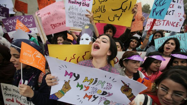 Woman carries a sign and chants slogans during a rally to mark International Women's Day in Lahore