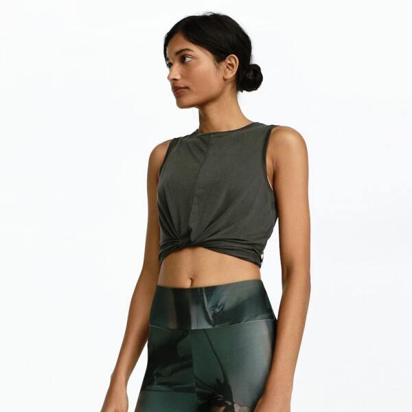 Una playera sin mangas en verde seco (básico) que combine con el estampado de tus leggins, muestra ese six pack, con el detalle del top que aparenta un nudo adelante.  Oysho.com / Top: $449, leggins: $799