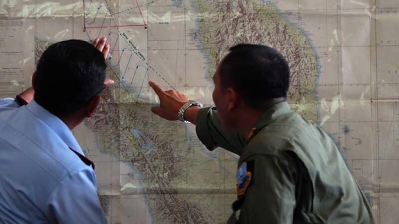 Autoridades de Indonesia observan un mapa de la ruta del avión desaparecido
