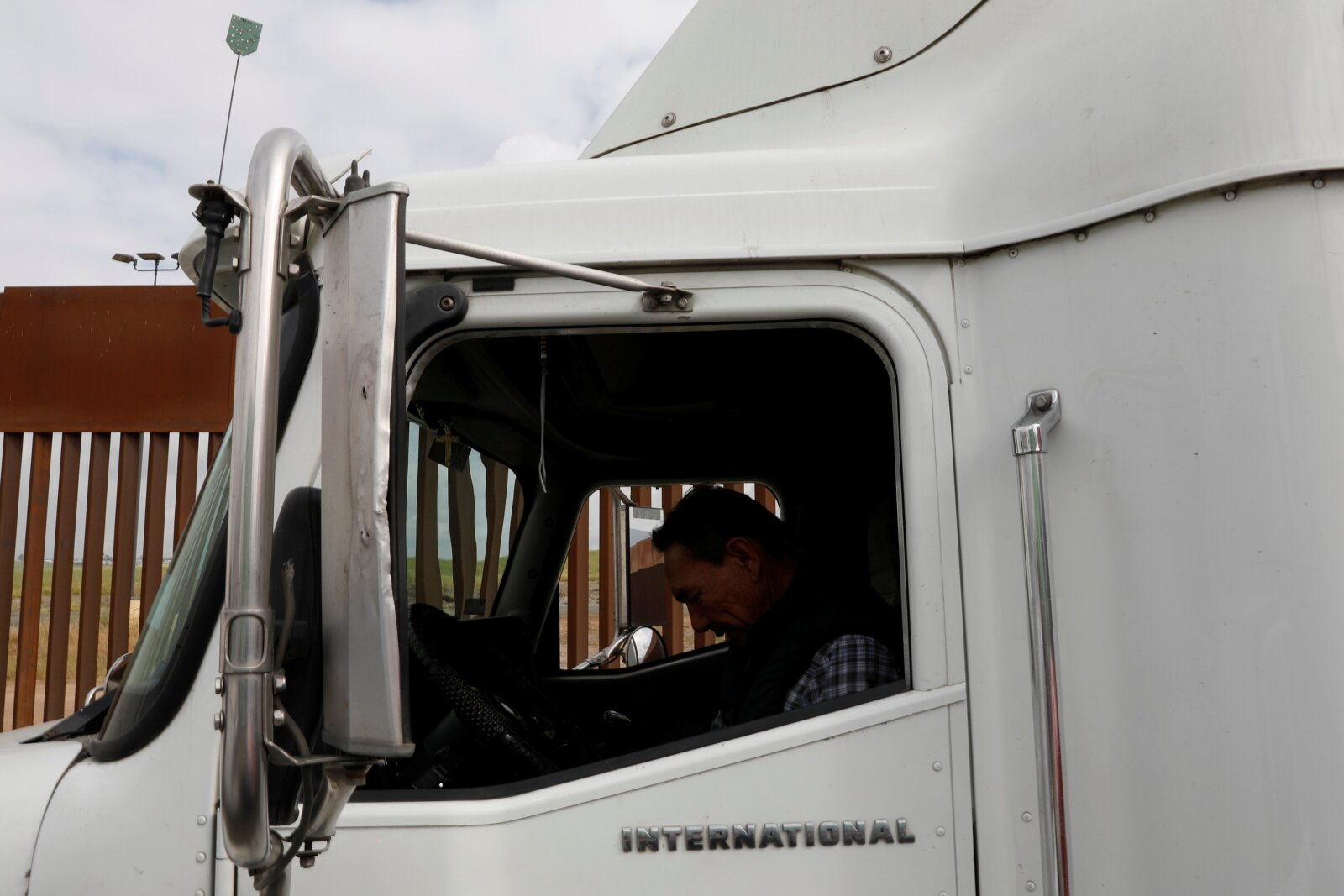 A truck driver waits in a long queue for border customs control to cross into the U.S., at the Otay border crossing in Tijuana