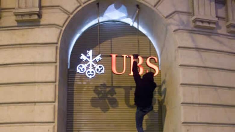 Un activista se colgó del logo de una sucursal del banco suizo UBS en Basilea para protestar contra la cumbre económica que se realiza en Davos. (Foto: Reuters)