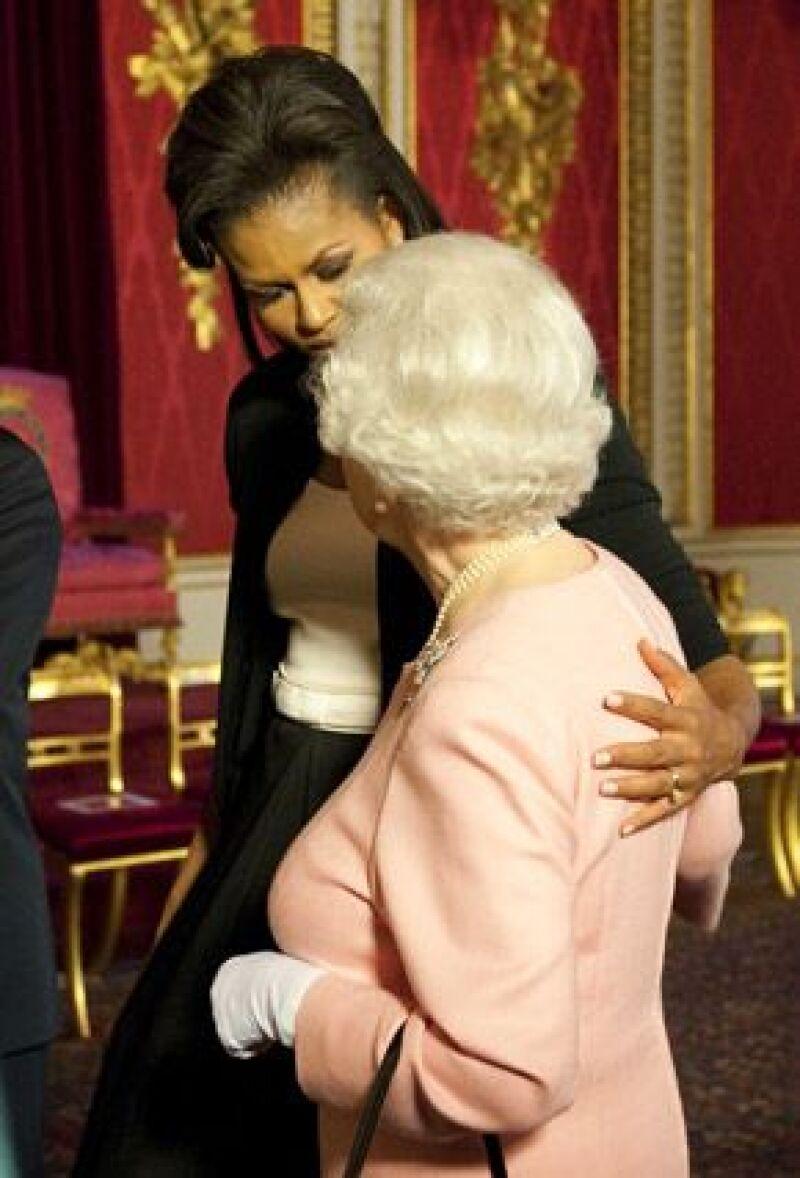 Pese a que está prohibido tocar a la soberana, la primera dama de EU respondió a un gesto de Isabel II y la rodeó con uno de sus brazos; la monarca no demostró ningún signo de molestia.